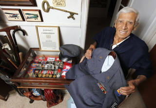 Simon, with his medals, Governor's commendation and Air Force uniform, is seen Friday at his home in Oklahoma City. PAUL B. SOUTHERLAND -