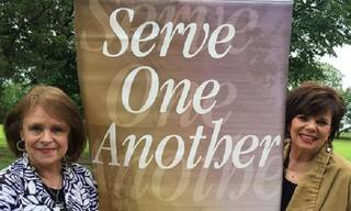 """Revive Inc. board member Carol Wright, left, and President Cynthia Huffmyer stand in front of the """"Serve One Another"""" banner at a volunteer site hosted recently by The Bethel Foundation. PHOTO PROVIDED - Photo provided"""