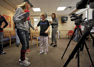 Angela Tygard helps her daughter Ambri walk back to her wheelchair after speaking to the media about her injuries and experience of being trapped under an elevator with two other girls at Classen School of Advance Studies during a news conference at the OU Medical Center Children's Hospital on Thursday, Nov. 17, 2011. in Oklahoma City. Photo by Chris Landsberger, The Oklahoman CHRIS LANDSBERGER