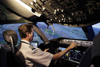 American Airlines pilot Bill Elder, the airline's fleet training manager on the Boeing 787 Dreamliner, banks sharply to the left over the Queens and Manhattan boroughs of New York in a Boeing 787 flight simulator in Fort Worth, Texas. AP Photo LM Otero - AP