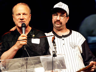 Billy McLane (right) holds his award as he gives Barry Switzer a hug after Switzer named Billy Special Olympics Oklahoma's Athlete of the Year during the opening ceremonies for the Special Olympics at Gallagher-Iba arena in Stillwater, Wednesday, May 10, 2006. By John Clanton, The Oklahoman