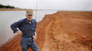 Angler Joe Myers stands in the reddish silt that until recent years was the bottom of Canton Lake. Myers had been casting in a shallow strip of water near the dam on Wednesday, May 21, 2014, when this photo was taken. He says the water depth where he is standing should be between 8 and 10 feet when the lake is at its normal levels. A sustained drought combined with the release of millions of gallons of water downstream to Oklahoma City in 2013 has caused large sections of the lake to dry up and has extended the lake's shoreline by hundreds of feet. Photo by Jim Beckel, The Oklahoman