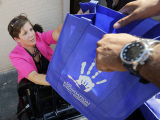 Christine Cooper, a fifth-grade teacher at Cesar Chavez Elementary, hands a bag of school supplies to volunteer Tagzmin Cudjoe as Cooper picks up supplies for her school at the Foundation for Oklahoma City Public Schools. The foundation, through its Teachers Warehouse program, recently reached the $1 million mark for giving away school supplies. Photo by Nate Billings, The Oklahoman NATE BILLINGS - THE OKLAHOMAN