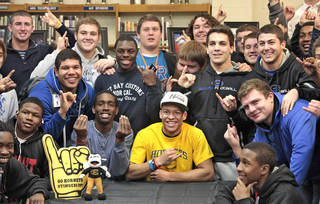 "Football player Kai Callins, center in yellow, holds up the ""Stingers Up"" sign with his teammates during his signing to play for Emporia State at Guthrie High School, Wednesday, February 4, 2014. Photo by David McDaniel, The Oklahoman"