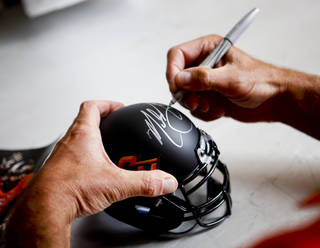 Oklahoma State head coach Mike Gundy signs a miniature helmet at fan appreciation day at Gallagher-Iba Arena in Stillwater on August 3, 2013. KT King, For The Oklahoman