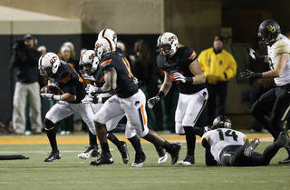 Oklahoma State cornerback Tyler Patmon, far left, comes up with a fumble recovery in the fourth quarter of an NCAA college football game against Baylor in Stillwater, Okla., Saturday, Nov. 23, 2013. Patmon returned the ball for a touchdown. Oklahoma State won 49-17. (AP Photo/Sue Ogrocki)