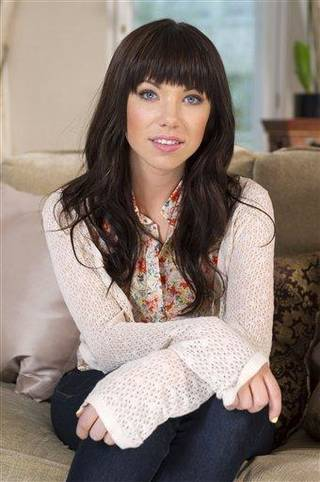 In this photo taken on Thursday, April 19, 2012 Canadian singer, Carly Rae Jepsen, poses for photographs following an APTN interview at the Landmark Hotel, London. (AP Photo/Jonathan Short)