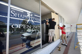 Geoff Hampton and Larry Copeland board up a window at Shapes Fitness center that was broken in an early morning earthquake in Harrah on Tuesday. Photo by David McDaniel, The Oklahoman David McDaniel