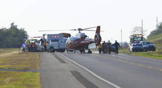 Mediflight crew transports the driver of a pickup truck that hit a Chickasha School bus on State Highway 62 east of Chickasha, Monday, October 15, 2012. The truck is being loaded on a wrecker on the left and the gurney with the victim is on the right. Photo By David McDaniel/The Oklahoman