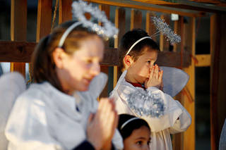 Left: Kenny Larson, 7, stands in as an angel during a living nativity pageant at the Oklahoma City church. PHOTO BY BRYAN TERRY, THE OKLAHOMAN