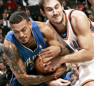 Oklahoma City's Nenad Krstic and Orlando's Matt Barnes battle for a loose ball during the Thunder's 102-74 win Sunday in the Ford Center. PHOTO BY JOHN CLANTON, THE OKLAHOMAN