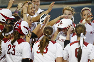 The OU team celebrates with Shelby Pendley as she crosses home after hitting a home run in the sixth inning of a Bedlam softball game between the University of Oklahoma and Oklahoma State University in Norman, Okla., Wednesday, April 2, 2014. Oklahoma won 2-0. Photo by Bryan Terry, The Oklahoman