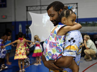 Jamaal Jackson dances with his daughter Julia, 4, during a Daddy-Daughter Dance at the Moore Community Center on Saturday. SARAH PHIPPS - SARAH PHIPPS