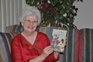 """Author LaNelma Johnson poses for a picture with her book, """"Okie in a Saree."""" Photo provided"""