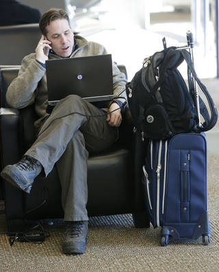 Scott Maish waits for his flight Tuesday, Nov. 26, 2013, at Will Rogers World Airport in Oklahoma City. Photo By Steve Gooch, The Oklahoman Steve Gooch - The Oklahoman