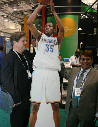 Visitors to the Oklahoma booth at the BIO International convention Wednesday pose with an image of Thunder player Kevin Durant. Both men said they were fans. PHOTO BY JIM STAFFORD