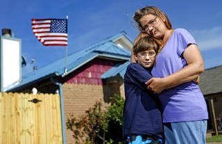 Karey Link and her son Gavin Cleary, 11, stand outside their Moore, Okla., home on Tuesday, Jun11, 2013. Karey's home and her neighbors were damaged by the May 20 tornado that hit Moore and was offended by the actions of the tornado chasing tour company Extreme Tornado Tour. Photo by Bryan Terry, The Oklahoman