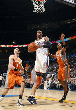 Oklahoma City's Russell Westbrook (0) shoots a lay up as Phoenix's Marcin Gortat (4) and Channing Frye (8) defend during the NBA game between the Oklahoma City Thunder and the Phoenix Suns, Sunday, March 6, 2011, the Oklahoma City Arena. Photo by Sarah Phipps, The Oklahoman.