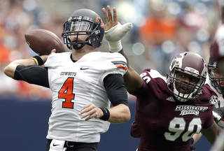 Oklahoma State's J.W. Walsh (4) throws a pass as he is pressured by Mississippi State's Denico Autry (90) during second half of the AdvoCare Texas Kickoff college football game between the Oklahoma State University Cowboys (OSU) and the Mississippi State University Bulldogs (MSU) at Reliant Stadium in Houston, Saturday, Aug. 31, 2013. Photo by Sarah Phipps, The Oklahoman