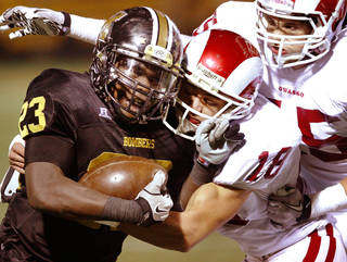 HIGH SCHOOL FOOTBALL: Owassso tacklers Alex Aucoin, 18, and Jantzen Burd , 45, shove Bomber running back Qualan Johnson out of bounds after a big gain in the first half during Class 6A playoff game between Midwest City Bombers and the Owasso Rams at Jim Darnell Stadium in Midwest City, Friday night, Nov. 18, 2011. Photo by Jim Beckel, The Oklahoman