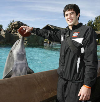 Oklahoma State quarterback Zac Robinson holds a football on the nose of Crunch, an Atlantic bottlenose dolphin, during a Holiday Bowl team event held at Seaworld, Saturday, Dec. 27, 2008, in San Diego. Oklahoma State will face Oregon in the Holiday Bowl NCAA college football game Tuesday, Dec. 30. (AP Photo/Denis Poroy)