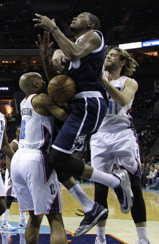 Oklahoma City Thunder's Kevin Durant, center, is fouled as he drives between Charlotte Bobcats' Gerald Henderson, left, and Josh McRoberts during the first half of an NBA basketball game in Charlotte, N.C., Friday, Dec. 27, 2013. (AP Photo/Chuck Burton)