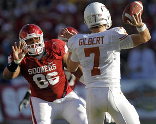 Oklahoma's Adrian Taylor, left, puts pressure on Texas quarterback Garrett Gilbert during the Red River Rivalry on Saturday, Oct. 2. PHOTO BY CHRIS LANDSBERGER, THE OKLAHOMAN