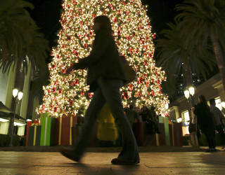 A holiday shopper walks past a large Christmas tree Dec. 20 at Fashion Island shopping center in Newport Beach, Calif. AP Photo
