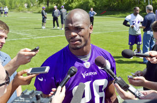 Minnesota Vikings running back Adrian Peterson (28) talks with reporters at the end of an NFL organized team activity at the Vikings football practice facility in Eden Prairie, Minn., Thursday, May 29, 2014.(AP Photo/Andy Clayton-King)