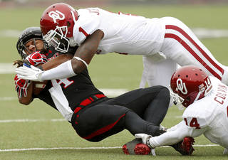 Texas Tech's Bradley Marquez (4) is brought down by Oklahoma's Tony Jefferson (1) and Aaron Colvin (14) during a college football game between the University of Oklahoma (OU) and Texas Tech University at Jones AT&T Stadium in Lubbock, Texas, Saturday, Oct. 6, 2012. Photo by Bryan Terry, The Oklahoman BRYAN TERRY - BRYAN TERRY
