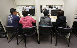 People are seen in March at the business office of Parkland Hospital in Dallas, using a phone bank to sign up for health insurance. AP File Photo LM Otero - AP