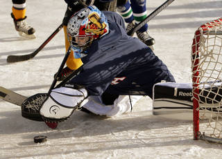 Ben Clark, 7, makes a save during an ice hockey game Saturday at the Norman Outdoor Holiday Ice Rink.