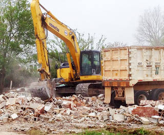 The former Tammy's Laundry building was torn down Tuesday at Littler Avenue and Hurd Street to make way for the new public safety center in downtown Edmond. The city's former administration building, at First Street and Littler Avenue, also will be demolished by Midwest Wrecking. PHOTO BY DIANA BALDWIN, THE OKLAHOMAN. Diana Baldwin - THE OKLAHOMAN