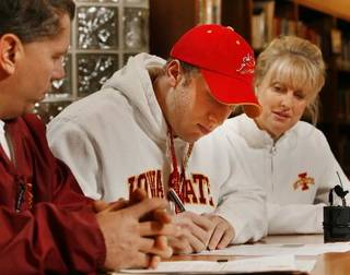 Beau Blankenship signs a letter of intent to play college football at Iowa State as his parents Charlie and Cynthia watch at Norman North High School in Norman, Okla. on Wednesday, Feb. 4, 2009. Photo by Steve Sisney