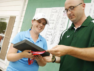 Edmond North's Allison Sell receives her trophy as the best individual player from Tournamnet Manager Kevin Hogue at the Class 6A Girls State Golf tournamnet at Muskogee Country Club in Muskogee, Okla. taken on May 3, 2012. JAMES GIBBARD/Tulsa World