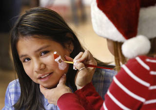 Desirea, 9, has a Santa face painted on her by Kelly Long, a volunteer from TLC Custom Homes.