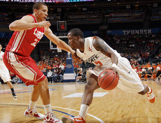 OSU's Reger Dowell (5) tries to drive past Phillip McDonald (23) of UNM in the first half during the Bill Russell men's college basketball game of the Ramada All-College Classic between the Oklahoma State University Cowboys and the University of New Mexico Lobos at the Chesapeake Energy Arena in Oklahoma City, Saturday, Dec. 17, 2011. Photo by Nate Billings, The Oklahoman