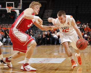OSU's Keiton Page (12) tries to get past Hugh Greenwood (3) of UNM in the second half during the Bill Russell men's college basketball game of the Ramada All-College Classic between the Oklahoma State University Cowboys and the University of New Mexico Lobos at the Chesapeake Energy Arena in Oklahoma City, Sunday, Dec. 18, 2011. UNM beat OSU, 66-56. Photo by Nate Billings, The Oklahoman