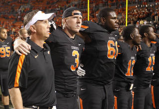 Oklahoma State quarterback Brandon Weeden, second from left, joins in with offensive coordinator Todd Monken, left, and teammate Michael Bowie, (61), as the team sings the alma mater with their fans following an NCAA college football game against Arizona in Stillwater, Okla., Thursday, Sept. 8, 2011. Oklahoma State won 37-14. (AP Photo/Sue Ogrocki) ORG XMIT: OKSO113