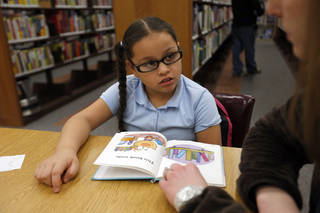 Left: Emily Lopez reads with Meagan Sheikh at the Capitol Hill Library. Photos by Sarah Phipps, The Oklahoman