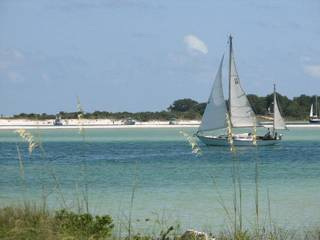 A sailboat goes searching for a breeze in Perdido Key, Fla. Photo by Ed Godfrey, The Oklahoman