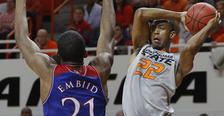 Oklahoma State's Markel Brown (22) passes the ball as Kansas' Joel Embiid (21) defends during an NCAA college basketball game between Oklahoma State University (OSU) and the University of Kansas at Gallagher-Iba Arena in Stillwater, Okla., Saturday, March 1, 2014. Oklahoma State won 72-65. Photo by Bryan Terry, The Oklahoman