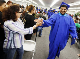 Graduate Ricky Izaguirre reaches for the hand of his mother, Angela Lopez, as graduates at the end of the ceremony for Emerson High School at the Oklahoma City campus of Langston University, Thursday, May 16, 2013. Emerson is an alternative education high school for students who need non-traditional learning because of a variety of reasons including teen pregnancy, homelessness and a need to work to support family. Photo by Nate Billings, The Oklahoman