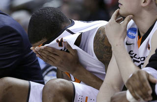 Oklahoma State forward Michael Cobbins covers his face during the second half of a second-round game in the NCAA college basketball tournament against Oregon in San Jose, Calif., Thursday, March 21, 2013. Oregon won 68-55. (AP Photo/Ben Margot) ORG XMIT: SJA128
