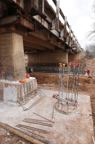Work is under way to correct erosion around the timber supports on the Sooner Road bridge, which was closed in September. Contractors are expected to be finished by the end of April. PHOTO BY PAUL B. SOUTHERLAND, THE OKLAHOMAN. PAUL B. SOUTHERLAND - THE OKLAHOMAN