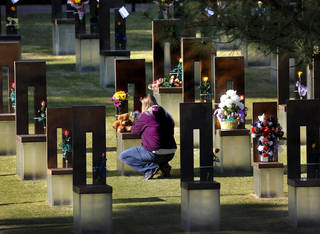 A woman places flowers and a stuffed animal on a chair before the start of the 19th anniversary Remembrance Ceremony at the Oklahoma City National Memorial Saturday morning, April 19, 2014, to honor the memory of the 168 victims killed in the 1995 bombing of the Murrah Federal Building. Photo by Jim Beckel, The Oklahoman