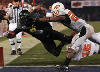 Oregon's LeGarrette Blount (9) dives into the end zone for a touchdown on a 29-yard run while Oklahoma State's Andre Sexton, right, and Perrish Cox (16) defend in the fourth quarter of the Holiday Bowl NCAA college football game in San Diego Tuesday, Dec. 30, 2008. Oregon won the game 42-31. AP Photo