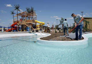 Above and below: Workers put finishing touches on landscape features at Andy Alligator's Water Park in Norman. PHOTOs BY STEVE SISNEY, THE OKLAHOMAN