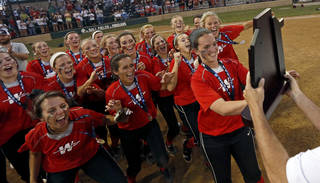 Washington players race to hoist the state championship trophy after beating Dale for the Class 4A state slowpitch softball championship in Shawnee on Tuesday. Photo by Bryan Terry, The Oklahoman