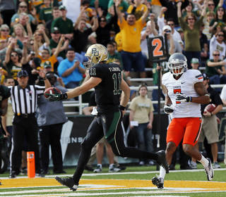 Baylor's Nick Florence (11) rushes for a touchdown past Oklahoma State's Shamiel Gary (7) in the second quarter during a college football game between the Oklahoma State University Cowboys (OSU) and the Baylor University Bears at Floyd Casey Stadium in Waco, Texas, Saturday, Dec. 1, 2012. Photo by Nate Billings, The Oklahoman
